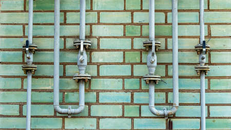 Pipeline with gas supply outlets on a green brick wall Foto de archivo - 153693891
