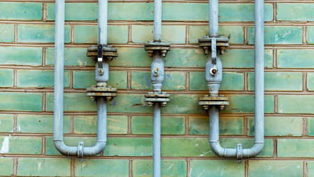 Pipeline with gas supply outlets on a green brick wall