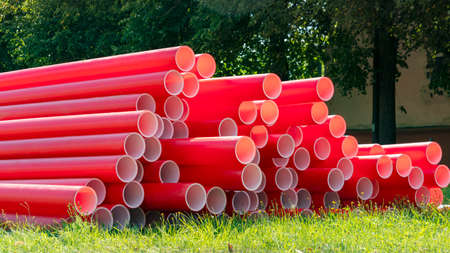red plastic pipes for sewage on a construction site