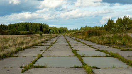the runway of an abandoned military airfield overgrown with grass Foto de archivo