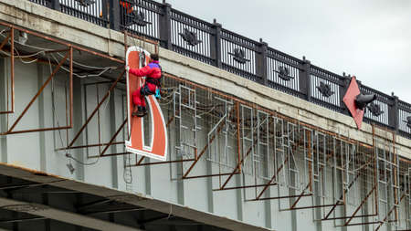 male industrial climber sets the inscription on the bridge