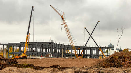 large construction site with high-rise cranes in cloudy weather