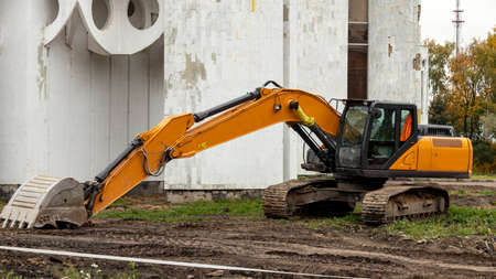 yellow excavator on a construction site with a lowered bucket Foto de archivo - 156945290