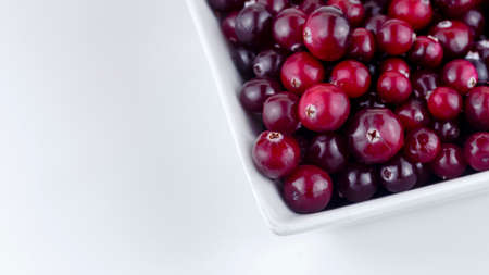 plate with ripe cranberries on a white background, macro photography, soft focus Foto de archivo