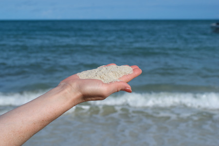 outstretched hand: White sand in the palm of an outstretched hand. Background - the sea, the waves