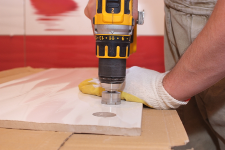 hand drill: Tile is on the desktop. Man holds in one hand a ceramic tile, other hand drill drill, which drills a hole in the tile.