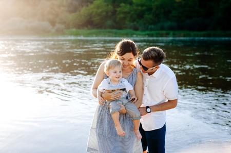 幸せな若い家族は、川で歩いてください。彼らは側面を観察します。彼らは笑顔し、笑い。喜ぶ