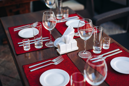 Beautifully decorated table. Preparation for dinner. Summer terrace. Cafe in the street. Clean dishes Stock Photo