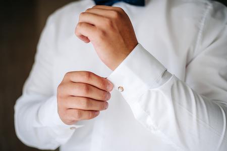 cufflink: Stylish man in a white shirt. The groom button up the cufflink. wedding day