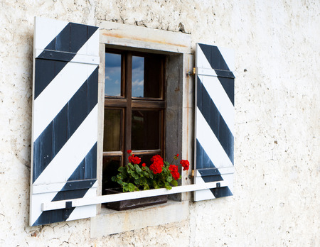 red shutters: Old wooden window with shutters and red flowers