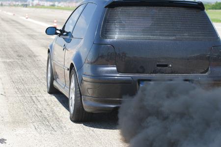 Verontreiniging van het milieu door brandbaar gas van een zwarte auto Stockfoto
