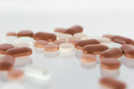 balanza de laboratorio: P�ldoras rojas y blancas aisladas en el fondo blanco Foto de archivo