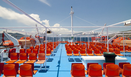 orange chairs: Empty orange chairs on the deck of the ferry