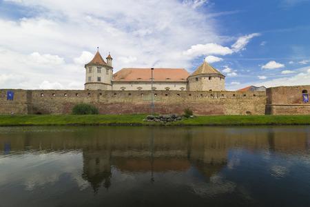 fagaras: Medieval walls surrounding an old castle and its reflection in the water, Fagaras,Transylvania, Romania