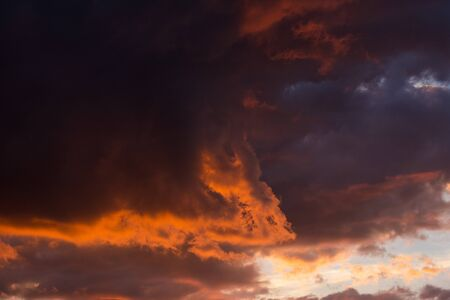 Storm clouds at sunset in bright colors Stock Photo