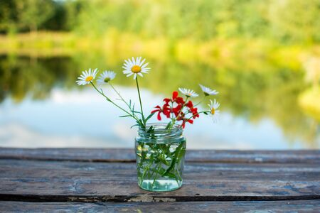 Daisies in a jar on a wooden table against a lake reflection Zdjęcie Seryjne
