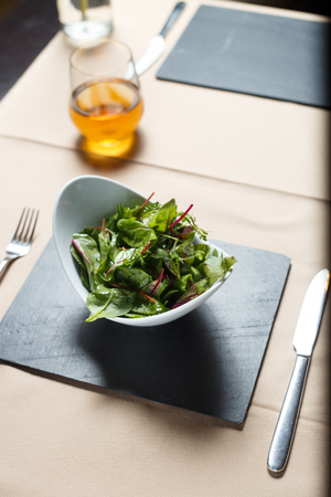 Salad in a white ceramic bowl on a black granite slab shot with artificial light Stock Photo