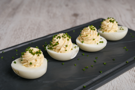 Eggs filled with cream cheese and garnished with parsley Imagens