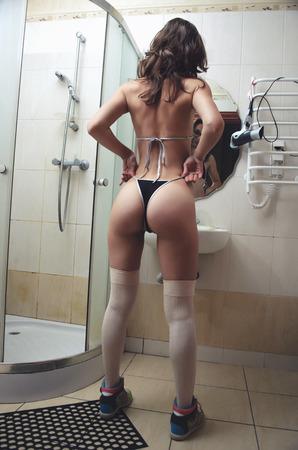 grosse fesse: Sexy jeune femme en culotte dans la salle de bain en plein écran. Femme avec un gros cul dans un bikini et bas, debout près d'un miroir.