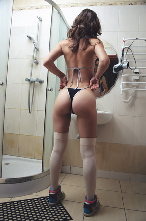 ass standing: Sexy young woman in panties in the bathroom in full view. Woman with a big ass in a bikini and stockings standing near a mirror. Stock Photo