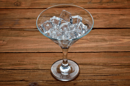 Glass of martini with ice cubes on wooden bar closeup. A glass of cocktail. Stock Photo