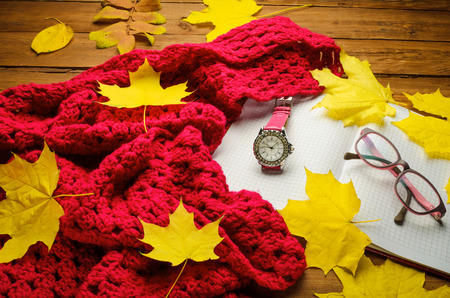 yellow notepad: Still life with a hot drink woolen scarf and a diary on a wooden table, autumn mood. Bright autumn: pink scarf and stylish clock on a wooden table with maple leaves.