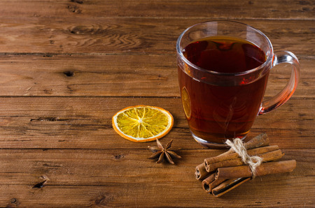 glass cup: Glass cup of tea, cinnamon and anise on a wooden background. Black tea and spices on a wooden table. Stock Photo