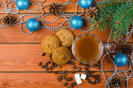 Christmas decorations and coffee on a wooden table. Fir branch, oat biscuits and a cup of hot coffee on a wooden background, top view. Stock Photo