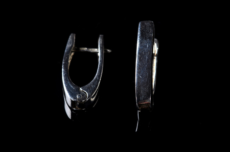 silver jewelry: Silver earrings isolated on a black background. Luxury jewelry closeup.