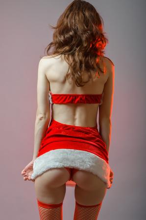 grosse fesse: Jeune et sexy fille père avec un gros cul. Femme en costume Snow Maiden, l'image de l'An, fond gris avec éclairage rouge.