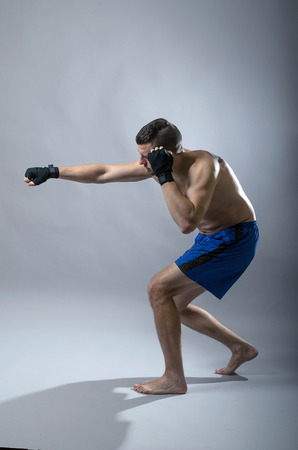 Portrait of kickboxer on a gray background. Martial Arts, Sports man strikes a fist. Stock Photo