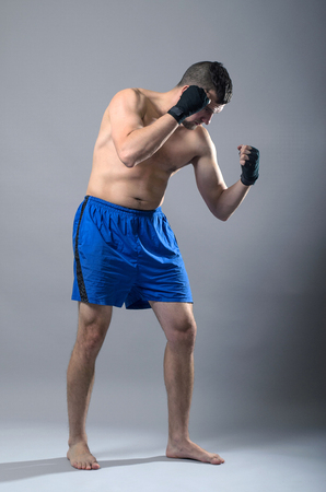 kickboxer: Portrait of kickboxer on a gray background. Martial arts, sports man in the guard position.