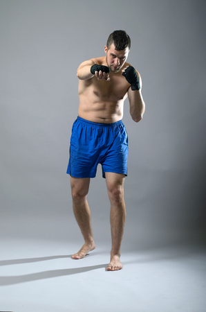 kickboxer: Portrait of kickboxer on a gray background. Martial Arts, Sports man strikes a fist. Stock Photo