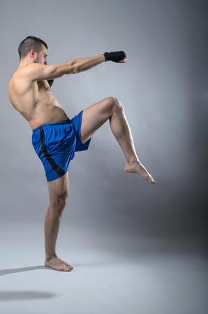 kickboxer: Portrait of kickboxer on a gray background. Martial Arts, Sports man kicks. Stock Photo