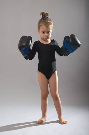Little girl in black tights and gloves for boxing on a gray