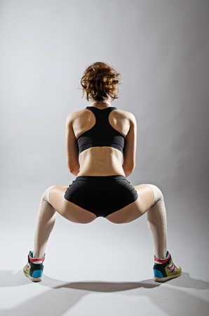 Slender young woman squats. Athletic woman in top and shorts on a gray background. Stock Photo
