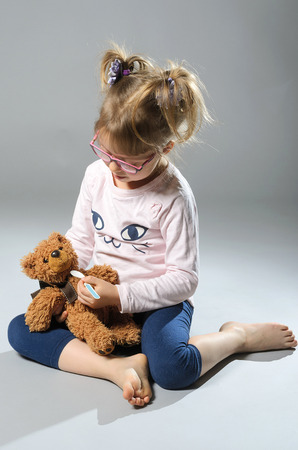 Pretty girl plays in the doctor treats a teddy bear on a gray background. Beautiful baby with a teddy bear.