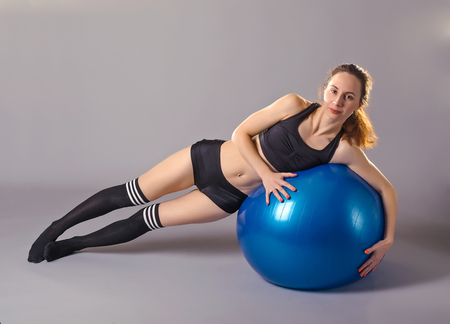 fitball: Young woman doing exercises on the fitball. Woman in the top, shorts and stockings on a blue fitball training, the photo on a gray background.