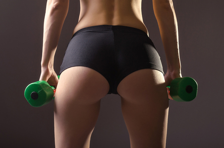 Womens ass in black shorts on a gray background. Sports woman with dumbbells in her hands.
