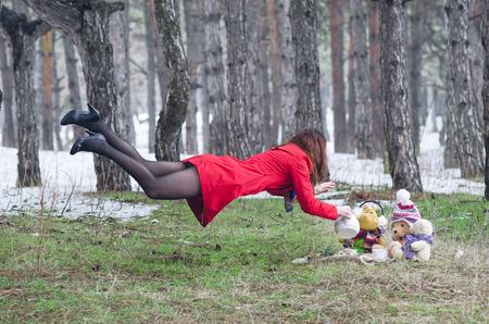 Mujer joven que vuela en el bosque con una caldera. El efecto de la mujer hermosa de levitación en un impermeable rojo vierte el carácter de cuento de hadas del té. Tea party animals en el bosque.