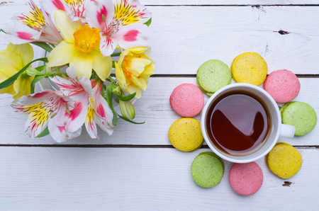 Multicolored macaroons, flowers and cup of hot tea on a wooden table. Spring composition, breakfast.