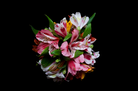 Bright bouquet on a black background, top view. Alstroemeria flowers on a black table.