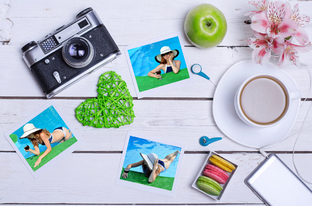 old photograph: Smartphone, old camera, tablet and summer photos on a wooden table, top view. The concept of summer vacation, and a cup of hot coffee on a wooden background.