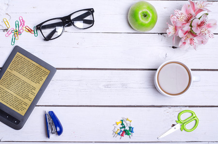 office stapler: Old office desk with gadgets, a cup of coffee, and a copy of the space in the middle. Office accessories: e-book, glasses, scissors, stapler, paper clips and buttons on a white wooden table, top view.