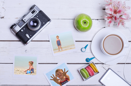 old photograph: Old photo camera, smartphone, headset and cup of coffee on a wooden background. The concept of summer holidays, family photos.