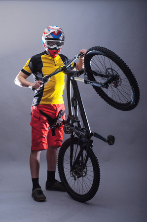 Portrait of a professional cyclist wearing a helmet on a gray background. MTB. Extreme sports, a cyclist posing with a bicycle.