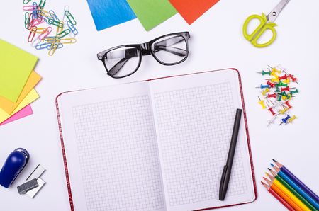 scissors: School and office supplies, notepad and glasses on a white background. Stationery, top view, free space. Working space.
