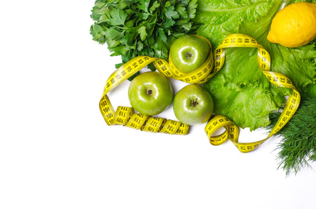 Concept of healthy eating on a white background: fresh salad and fruits. Salad, lemon and apples with measuring tape isolated on white, top view. Diet, free space. Stock Photo
