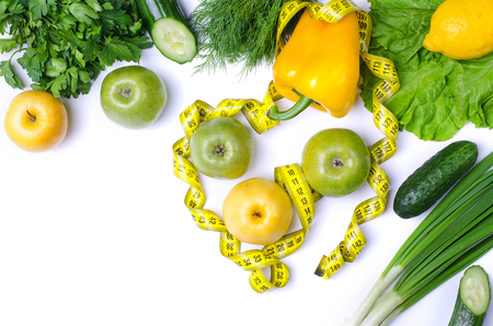 Diet, fruits and vegetables isolated on white, with copy space. Healthy eating, green apples and measuring tape, fitness. Stock Photo