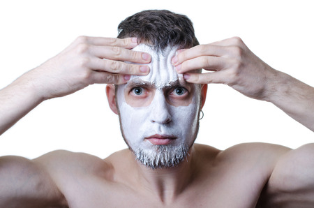 mimo: Young man with clay mask on his face, isolated on white. Portrait of a man with a cosmetic mask on his face, spa salon, facial.